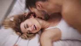 Una pareja retozando en la cama.
