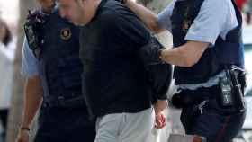 Juan López Ortiz es conducido al interior de su domicilio por los Mossos d'Esquadra
