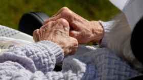 Una enferma de alzhéimer entrelaza sus manos.