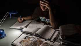 Un joven intenta estudiar ayudándose con la luz de un flexo.