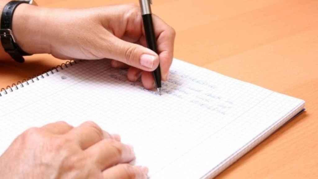 Una persona zurda escribiendo sobre un papel.