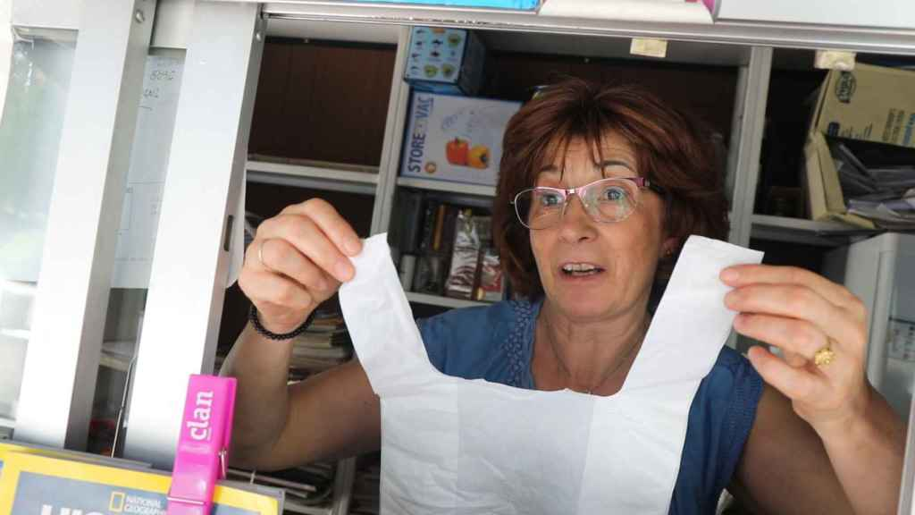 La encargada de una tienda muestra una bolsa de plástico.