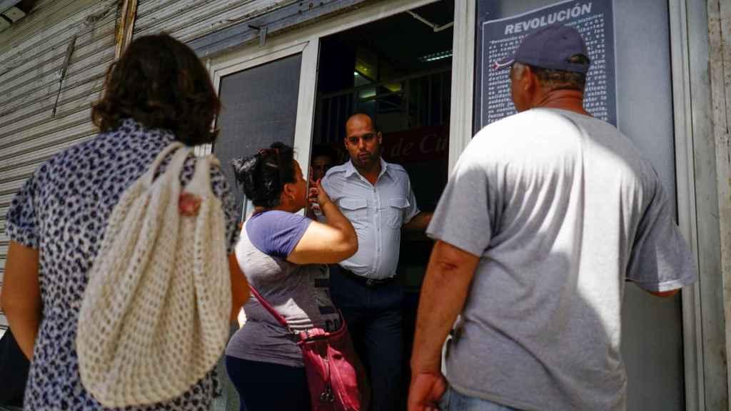 Algunos clientes pidiendo información a un empleado de Cubana.