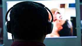 Un usuario delante de la pantalla del ordenador viendo un vídeo porno.