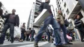 Varias personas cargadas con diversas compras, en una imagen de archivo.