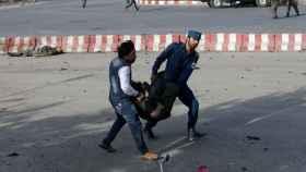 Dos miembros de seguridad evacuan a un herido; detrás, uno de los 15 fallecidos