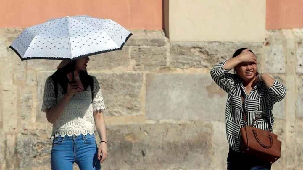 Dos jóvenes intentan combatir el calor en la localidad valenciana de Xativa.