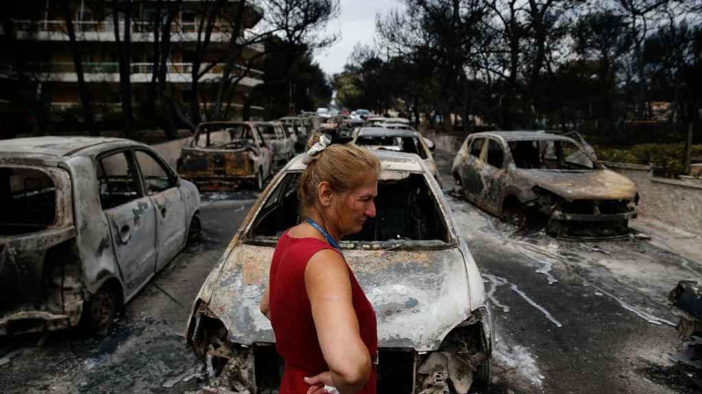 Una mujer observa los coches calcinados en las calles de la localidad griega de Mati.