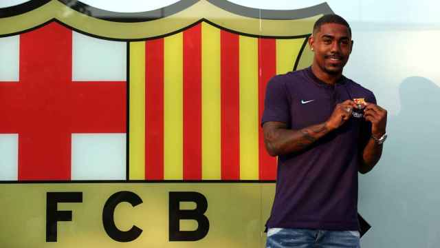 Brazilian soccer player Malcom Filipe Silva de Oliveira poses in front of a FC Barcelona logo at their offices next to Camp Nou stadium in Barcelona
