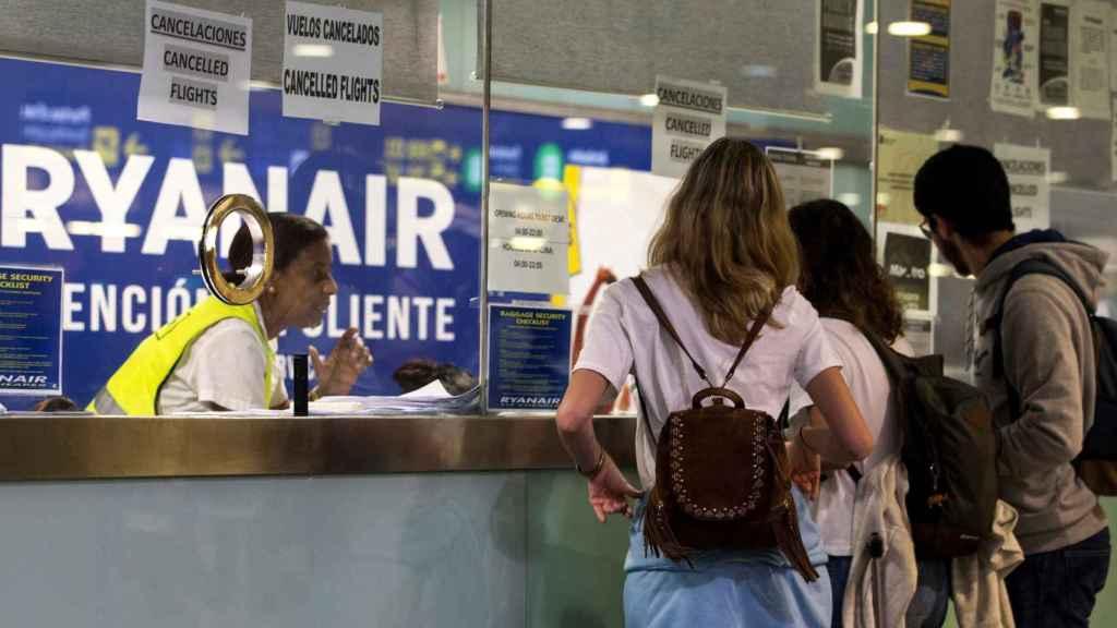 Varios pasajeros consultan información en el mostrador de Ryanair en El Prat.