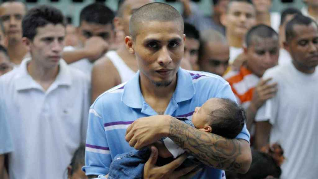 Un pandillero sujetando a un bebé.