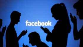 Gente consultando sus dispositivos móviles frente al logotipo de Facebook.