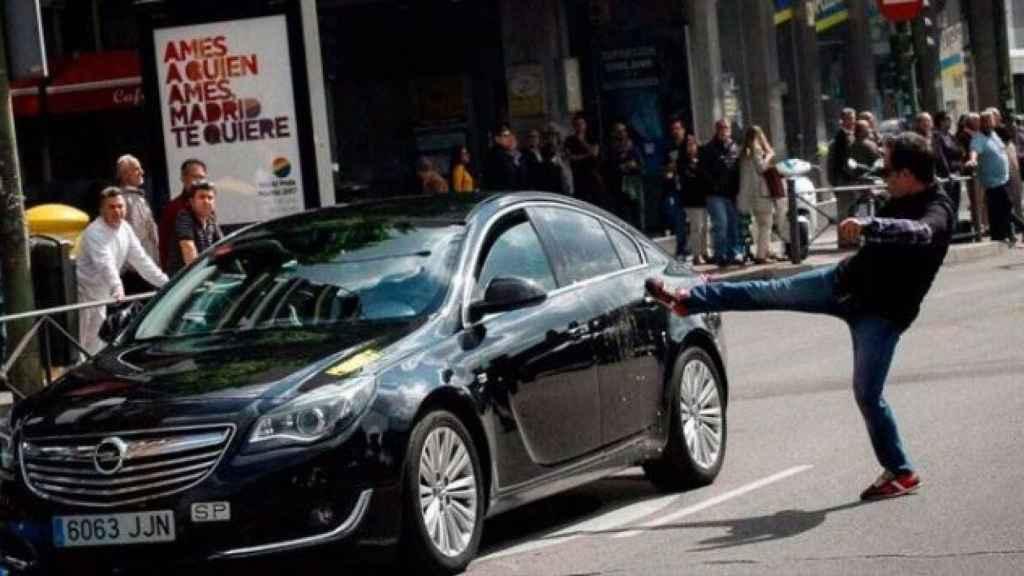 Un taxista en huelga propina una patada a un coche con licencia VTC .