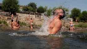 Un hombre se refresca en la zona fluvial del río Miño y las termas de A Chavasqueira, en Orense.
