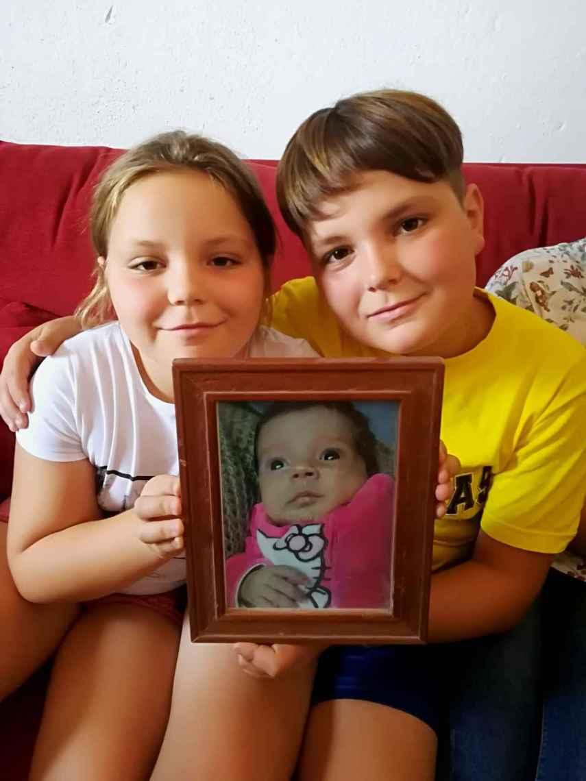Paqui, de nueve años, y Tomás, de 11, sostienen un retrato de su hermana Marta recién nacida. Hoy la niña tiene ya seis años.