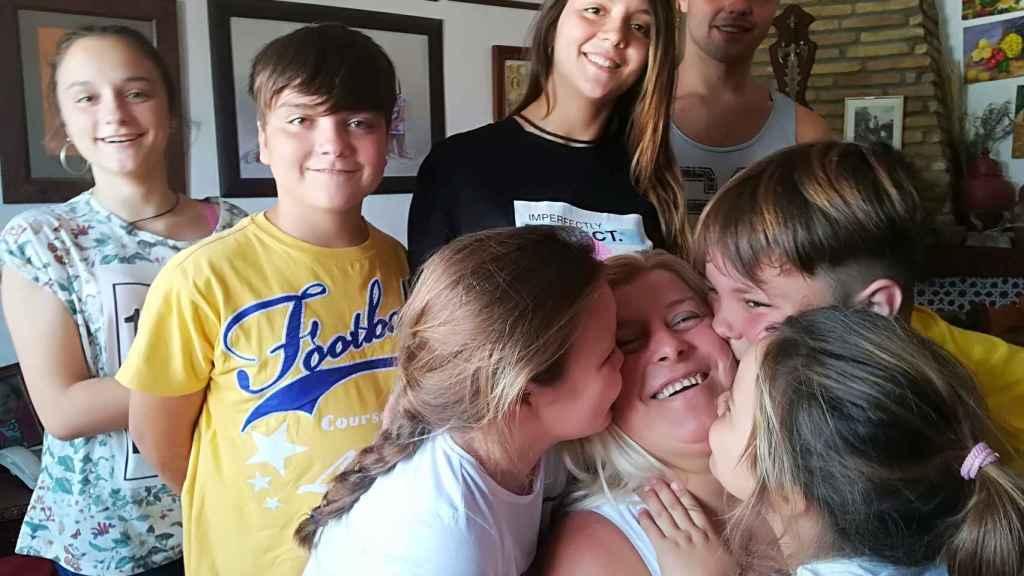 Paqui recibe el beso de tres de sus nietos.