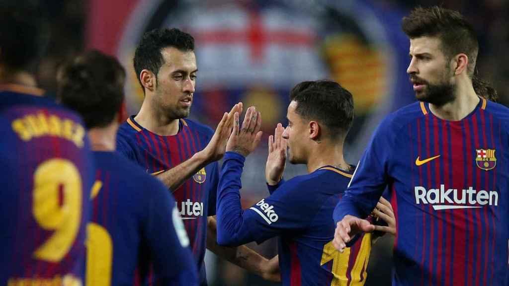 Busquets y Piqué, junto a Coutinho en un partido del Barcelona