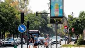 Varias personas pasan, este mediodía en la ciudad de Valencia, ante un termómetro urbano que marca una temperatura de 40º acompañados por la sensación de bochorno