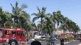 Los bomberos trabajan junto con la avioneta estrellada en un centro comercial de Santa Ana, Los Ángeles.