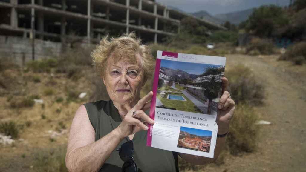 La ciudadana británica Ángela Jhon muestra el dossier que le entregaron al dar la entrada de un apartamento en la promoción Cortijo de Torreblanca. Foto Fernando Ruso