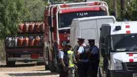Mossos y bomberos frente al camión con las bombonas de butano.