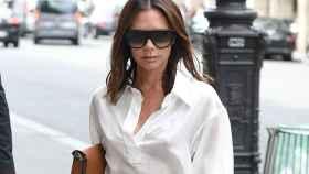 Victoria Beckham paseando por la calle con unas gafas de sol oscuras.