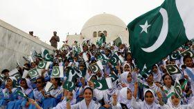 Participantes en las celebraciones del día de la independencia de Pakistán cantan canciones nacionales.