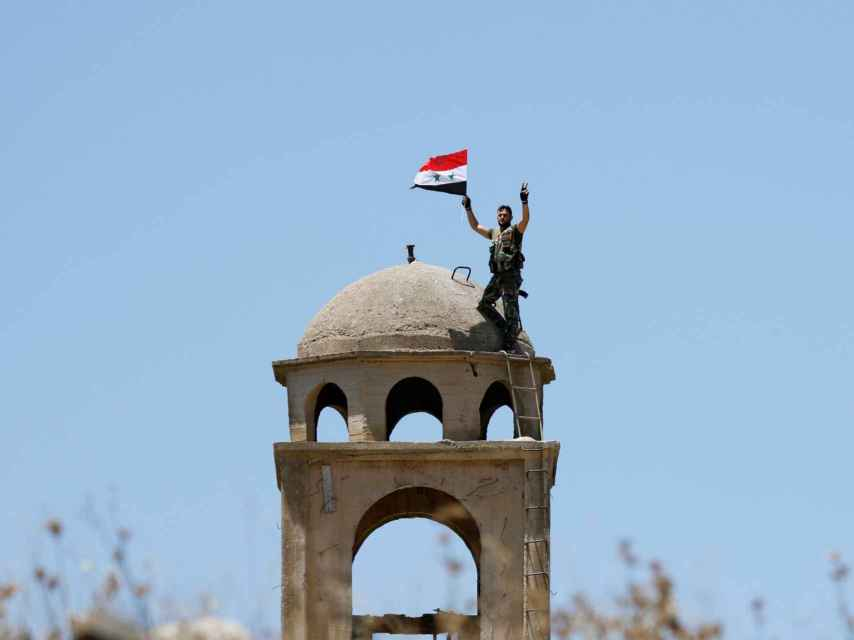 Un soldado sirio enarbola la bandera de su país.