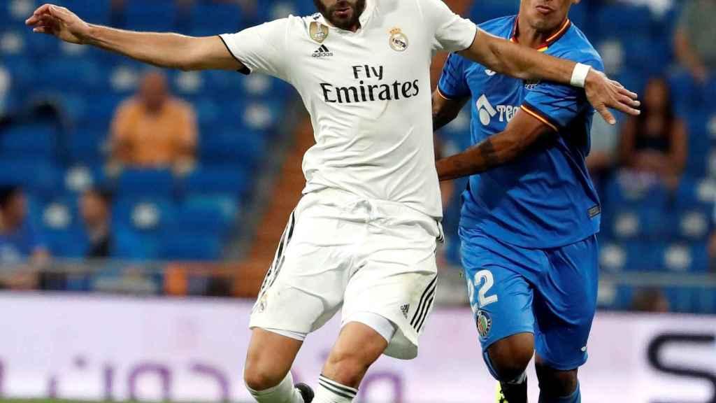 Karim Benzema, pugna por un balón con un jugador del Getafe.