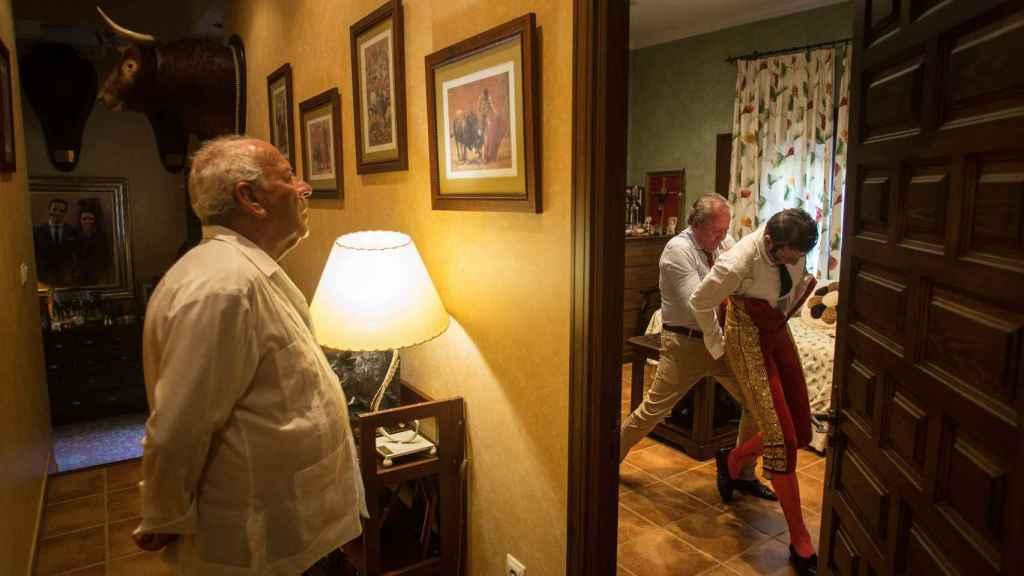Pepe Padilla, padre del torero, aguarda mientras su hijo se viste con el traje de luces.