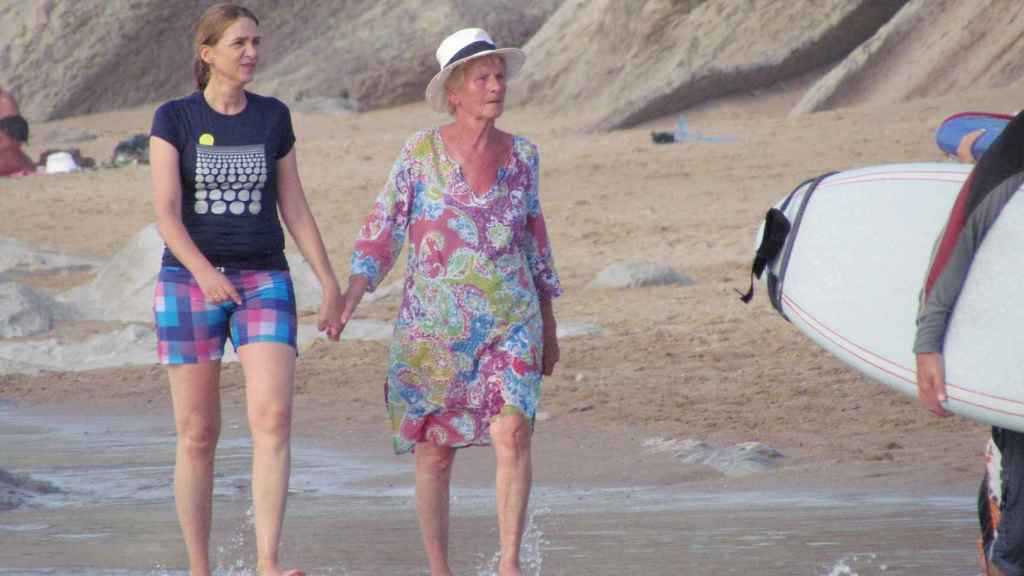 La infanta Cristina y Claire Liebaer paseando de la mano por la orilla del mar.
