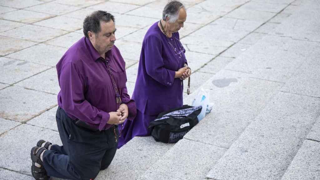 Dos religiosos rezando en las escaleras del valle durante el acto.