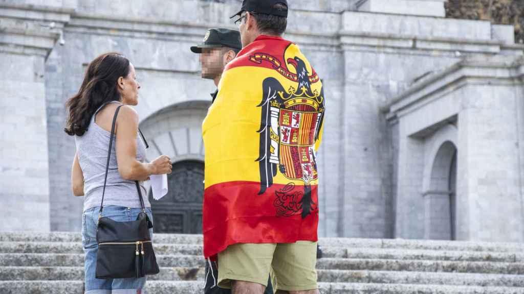 Uno de los asistentes a la vigilia del Valle de los Caídos luce la bandera franquista.