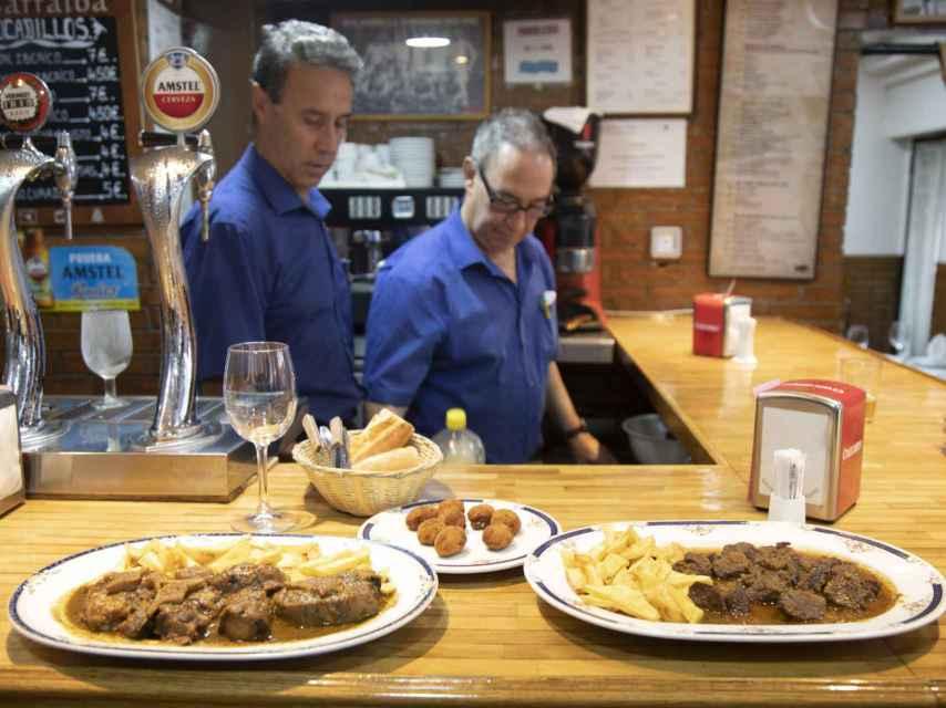 Antonio y Carlos trabajan tras la barra. En la barra, de izquierda a derecha: rabo de toro y canguro.