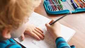 Niño escribiendo en un libro de texto