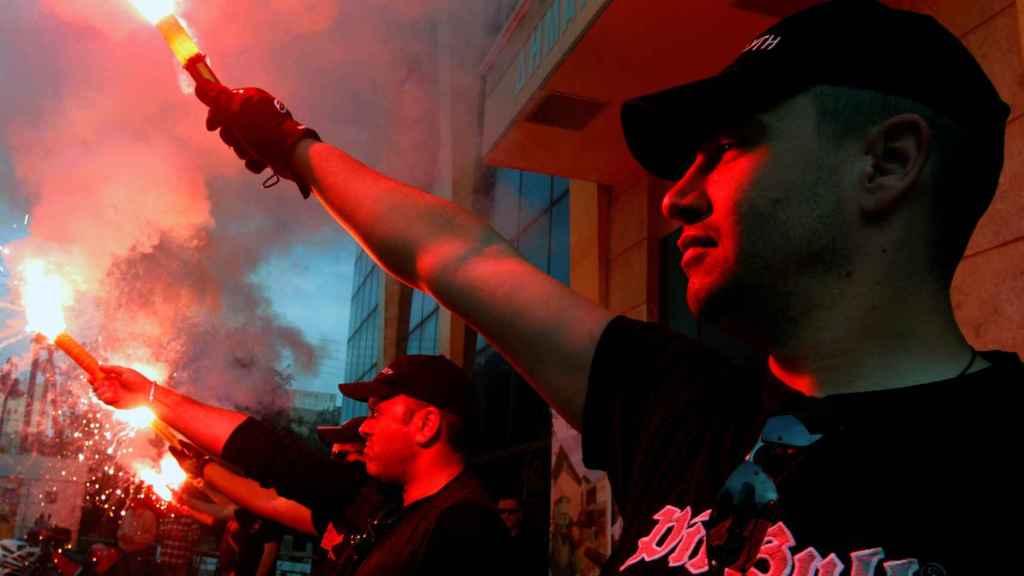 Miembros del partido griego de extrema derecha Amanecer Dorado, sosteniendo una bengala.