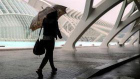Una persona se resguarda de la lluvia en la Ciudad de las Ciencias de Valencia.