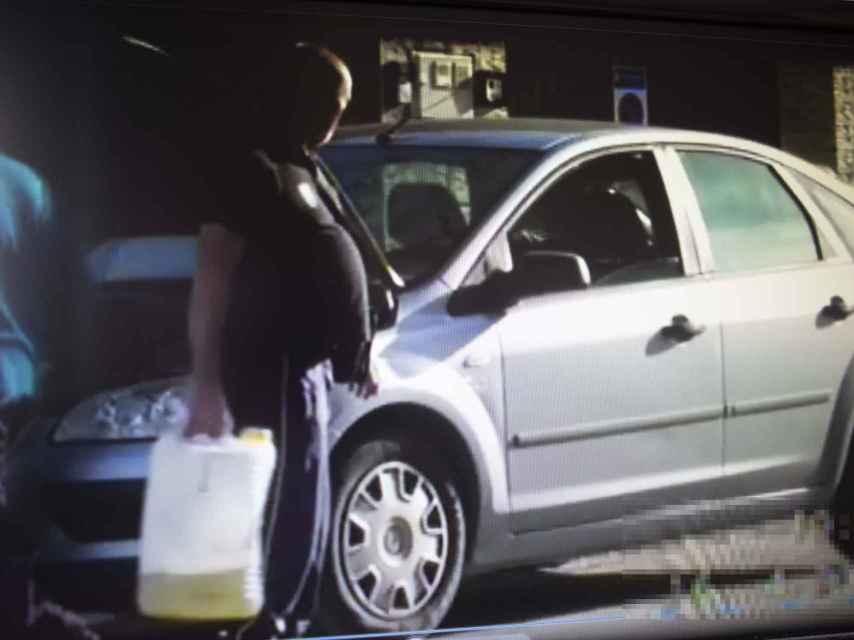 Un detective que siguió a este hombre durante varios días logró demostrar que trabajaba en un taller de coches como mecánico. En la imagen se le ve cargando con una garrafa de aceite delante del motor de un coche averiado.