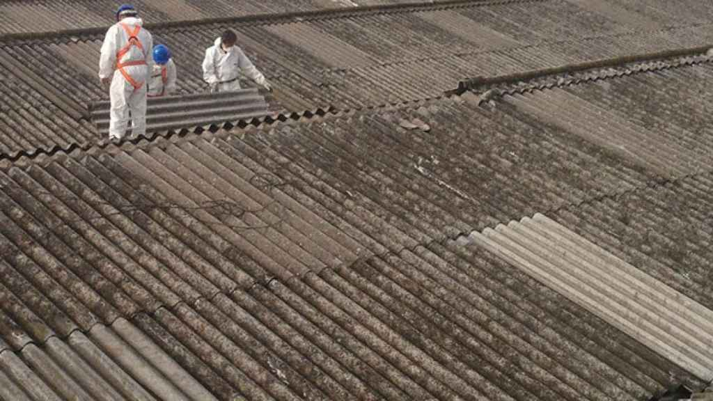Desde 2002, en España está prohibido el uso de amianto, que solía usarse para techados. En la imagen, dos operarios retirando un tejado de uralita.