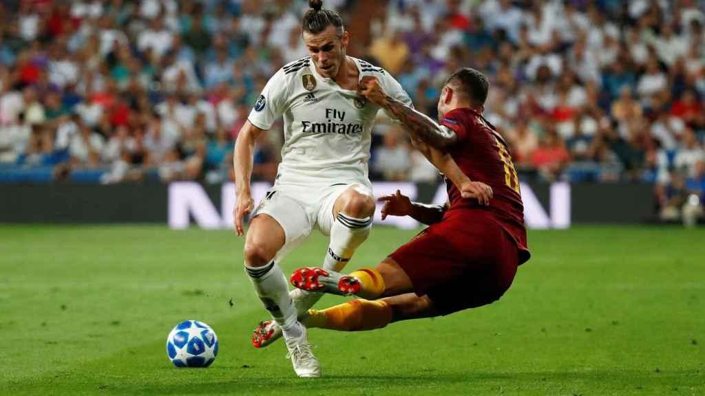 Gareth Bale agarrado por un jugador de la Roma