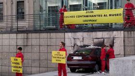 Los activistas de Greenpeace despliegan los carteles junto al coche empotrado.