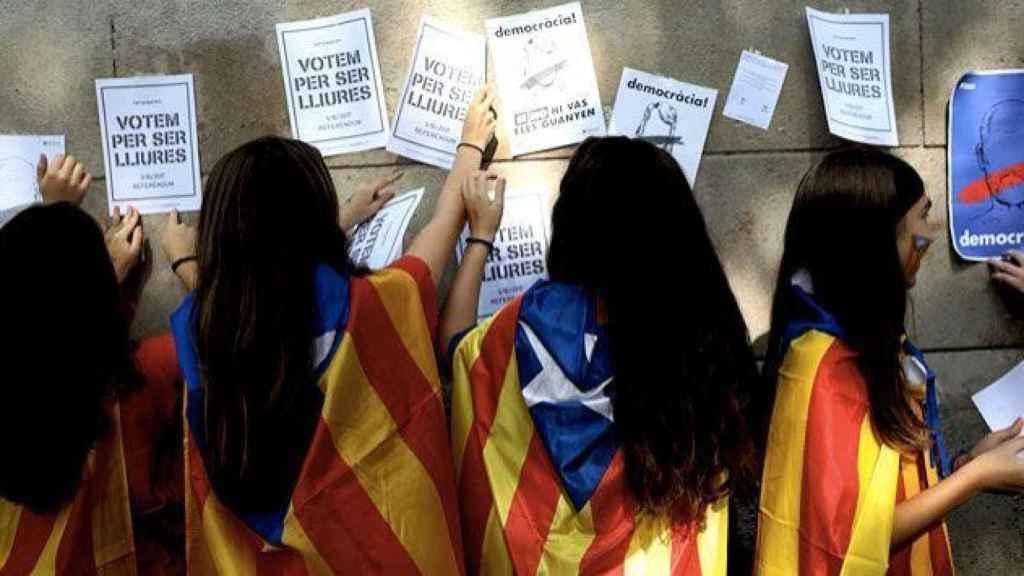Escolares catalanes pegan carteles a favor de la independencia.