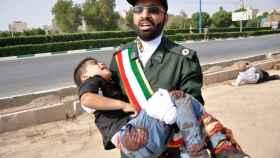 Un soldado iraní carga en brazos con un niño que resultó herido en el atentado terrorista en Irán.