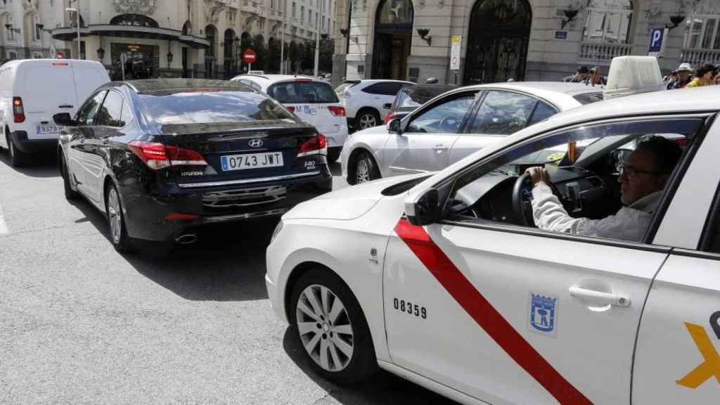 Un taxi detrás de un vehículo VTC en Madrid.