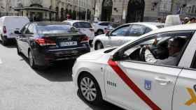 Un taxi de Madrid detrás de un vehículo VTC en las calles de Madrid.