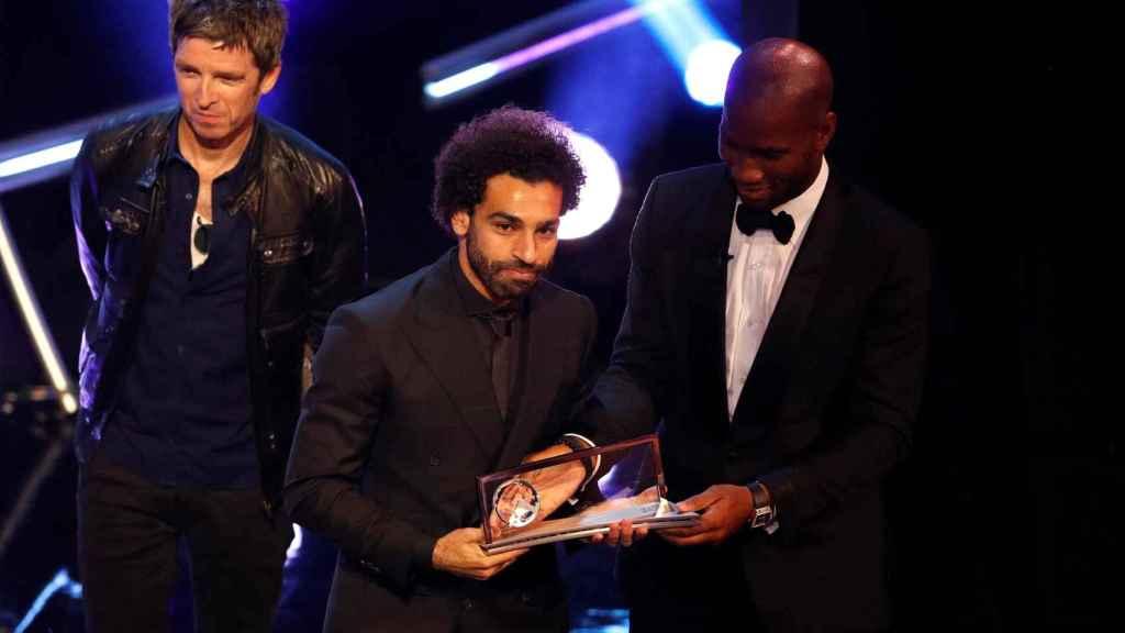 Salah recibe el premio por parte de Drogba.