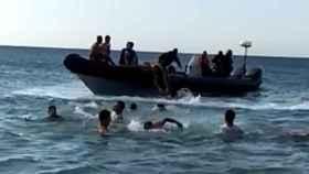 Grupo de inmigrantes marroquíes nadan para subir a bordo de una lancha como las que tradicionalmente usan los narcotraficantes para transportar hachís desde Marruecos hasta España.