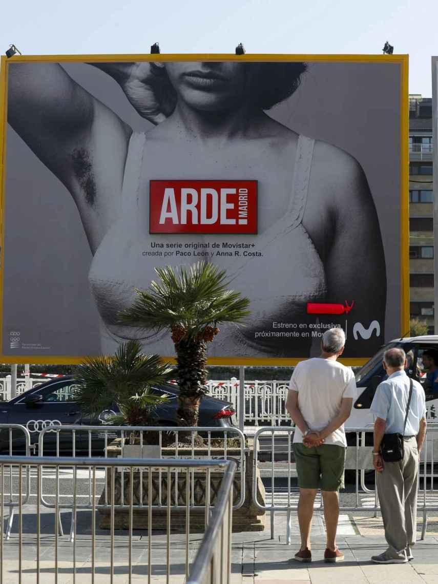 Unos hombres observan el cartel de la serie 'Arde Madrid' de Paco León.