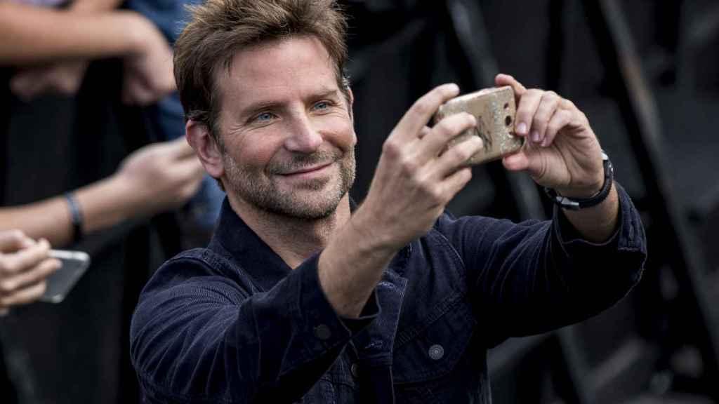 Bradley Cooper, con el móvil de una seguidora para hacerse un 'selfie'.