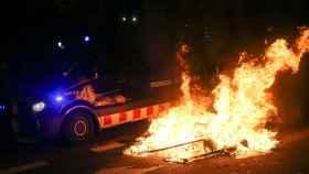 Momento en el que un coche de los Mossos pasaba anoche junto a una barricada situada frente al Parlament.